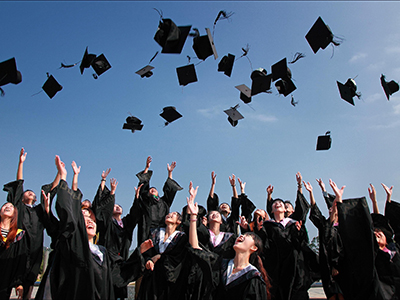 Graduating students tossing their mortarboards in the air